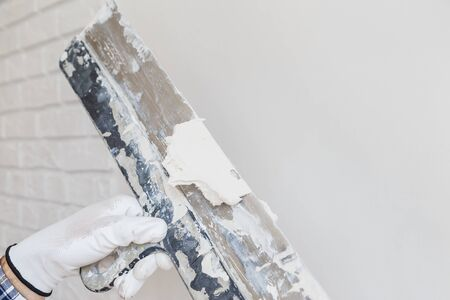 Worker in white gloves performs plastering of the walls in the room