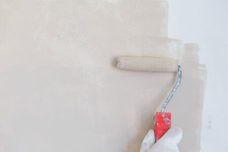 painter hand in white glove painting a wall with paint roller.