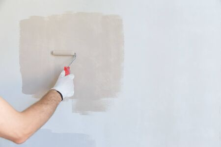 painter hand in white glove painting a wall with paint . Stockfoto