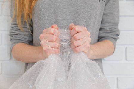 Female hands popping the bubbles in wrap. Selective focus, close up. Imagens