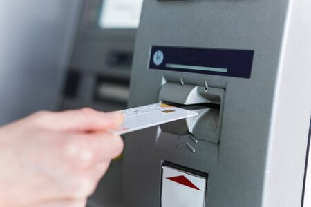 Person insert card to automated teller machine. Cashing non-cash money by individual