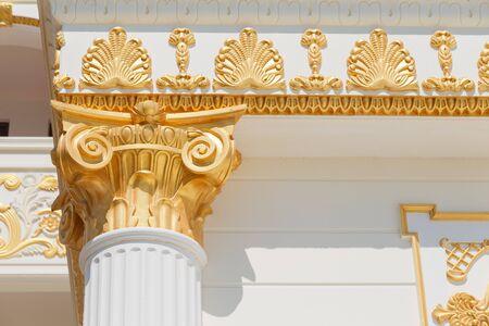 Top part of pillar, white column with golden top, exnterior detail. Banco de Imagens