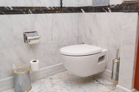 Hanging on wall white toilet bowl, grey natural marble.