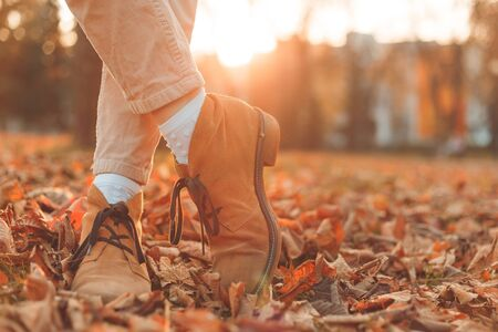 Women's legs in elegant autumn nubuck boots. At sunset in the city Фото со стока
