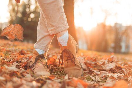 Women's legs in elegant autumn nubuck boots. At sunset in the city Foto de archivo