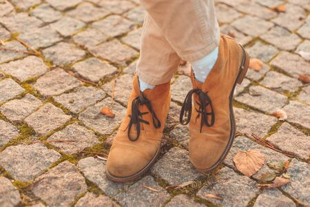 Women's legs in elegant autumn nubuck boots. At sunset in the city Imagens