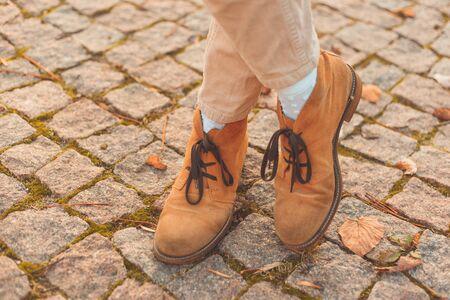 Women's legs in elegant autumn nubuck boots. At sunset in the city Standard-Bild