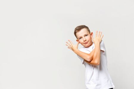 Carefree naughty caucasian boy grimaces. Portrait on an isolated background.