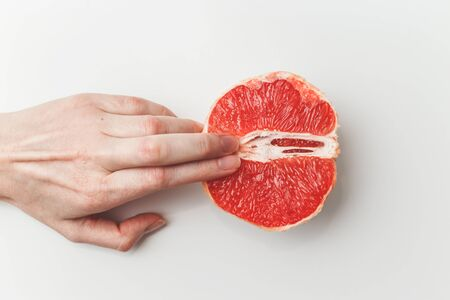 Sexual and female genital concept. Grapefruit and womens fingers like vagina and clitoris symbol