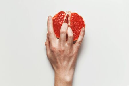 Sexual and female genital concept. Grapefruit and womens fingers like and clitoris symbol
