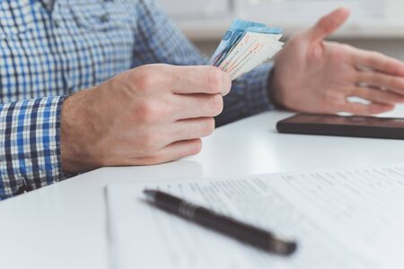 Tough financial conditions. Businessman holds money and gestures specifically. Stock Photo