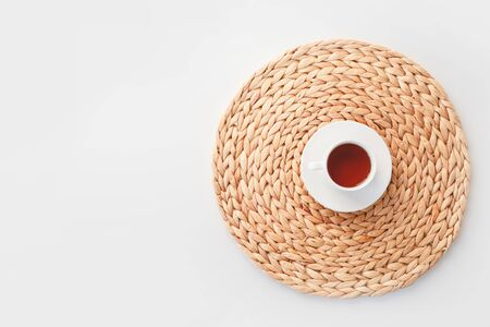 Cup of tea on round braided fibre placemat isolated on white, top view