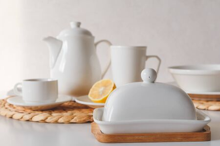 White ceramic tableware, fibre braided round placemat and cutlery set on white background. Scandinavian style.