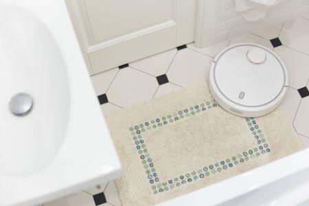 White robot vacuum cleaner on carpet in bathroom.