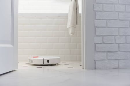 White robot vacuum cleaner in bathroom. Banque d'images