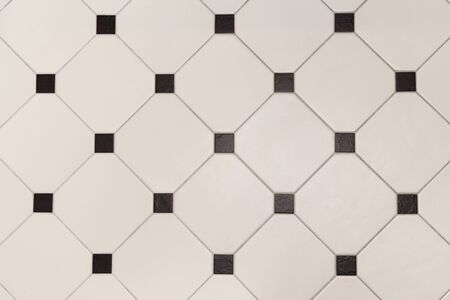 Ceramic beige octagon with tessellation black tiles background.