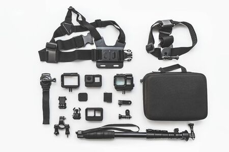 Flat lay of action camera with accessories on white background top view