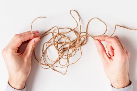 Man untangles a tangled thread. Top view isolated on a white background.