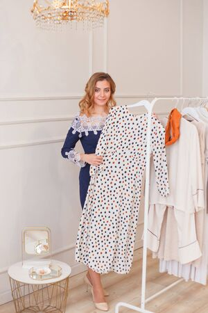 Young woman choosing polka-dot dress among clothes on a rack private showroom