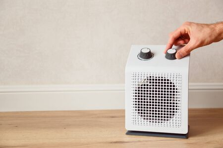 Man's hand adjusts the temperature of the electric fan heater at home in winter time. White domestic electric heater on floor indoor. Imagens