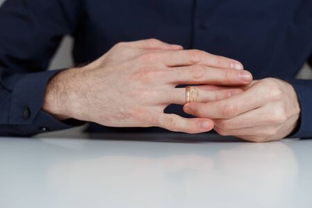 Young man is taking off the wedding ring. Close up view. Divorce concept. 版權商用圖片