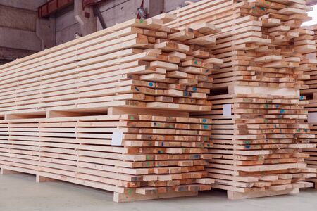 Warehouse or factory for sawing boards on sawmill indoors. Wood timber stack of wooden blanks construction material. Logging Industry.
