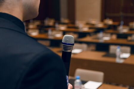 Microphone in the hand of a man in a suit on the background of an empty conference room. Rehearsal of public speaking. Фото со стока