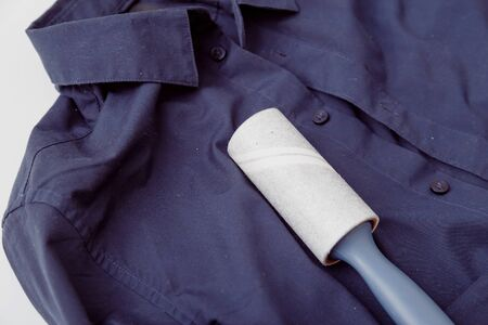 Dark color shirt with static cling, covered by dust, lint, fluff and hairs and sticky roller to clean clothes.