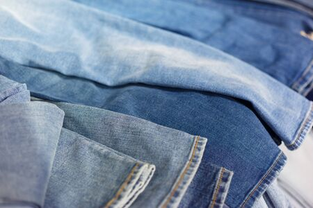 fashionable clothes. pile of jeans on a shelf in shop Banco de Imagens