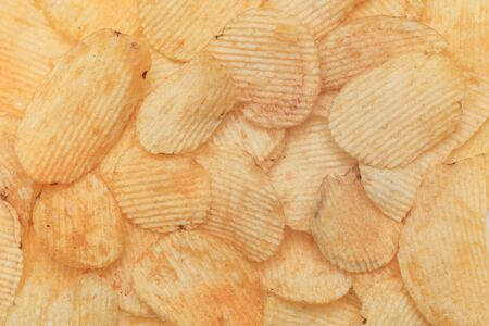 Potato corrugated chips texture background. Top view