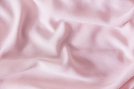 Pink wrinkled silk fabric. The pink fabric is laid out waves. Pink fabric background or texture