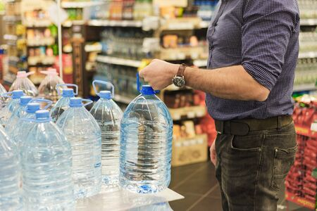 Man pick gallon bottle of drinking or distilling water at the shopping store.