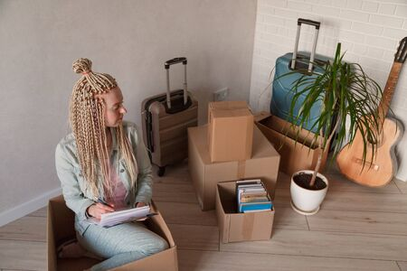 Beautiful woman sitting in box in casual clothes is packing her stuff into the boxes, making notes Фото со стока