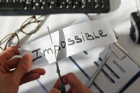 Businessman cutting the word impossible, letters im so it become possible