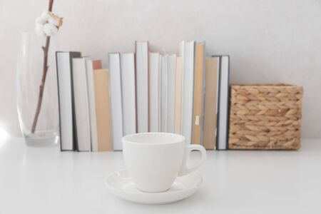 Bookshelf with books and cup of hot beverage in focus.