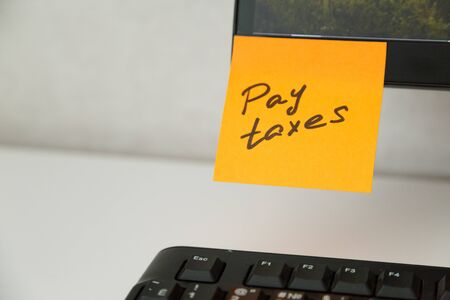 Reminder pay taxes sticked on monitor at freelancer's workplace. Finance planning concept
