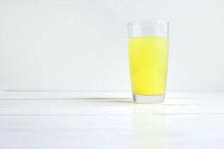 Glass of water with dissolved healthy vitamin tablet on white with copyspace.