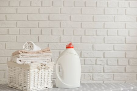 White plastic bottle with detergent gel and wicker basket with color clothes. Cleaning and laundry concept Standard-Bild