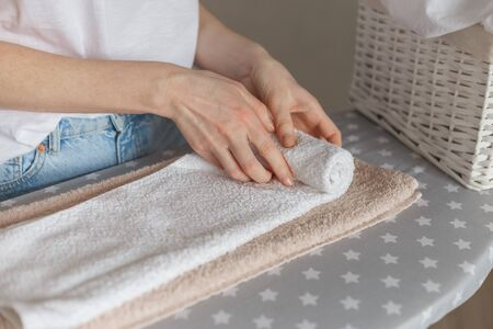 Woman rolling ironed clean towels standing at ironing board. Laundry service or cleaning housework concept Archivio Fotografico