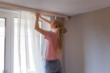 Young blonde woman hanging up curtains at the window