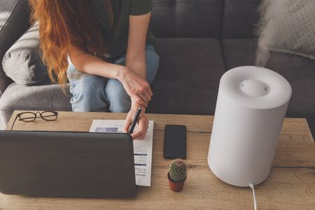 Woman freelancer uses a household humidifier in the workplace at home office with a laptop and documents.