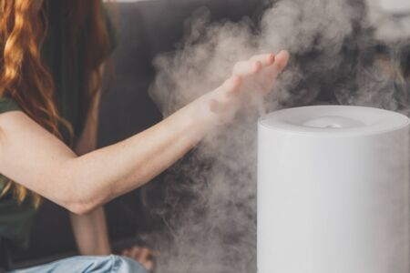 Healthy air. The humidifier distributes steam in the living room. Woman keeps hand over vapor.