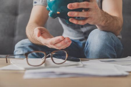 Man sitting at a table full of unpaid bills shakes out the last penny from the piggy bank. Spend your last savings. Unemployment, poverty, bankruptcy concept. Stockfoto