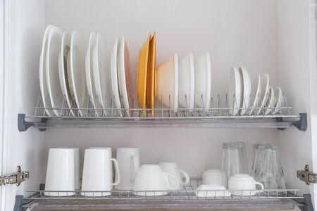 Dish drying metal rack with big nice white clean kitchenware. Traditional wall cabinet kitchen.