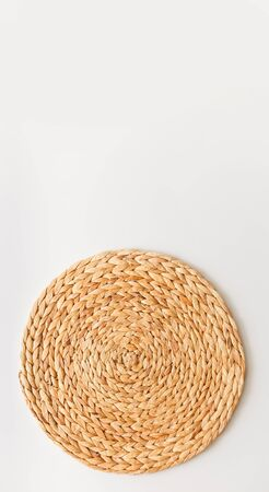 Wicker straw stand isolated on white background. Upright photo as flat lay, top view minimal social media template.