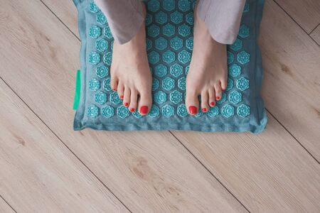 Female feet standing on acupressure mat. Self acupuncture massage. Woman having alternative medicine treatment.