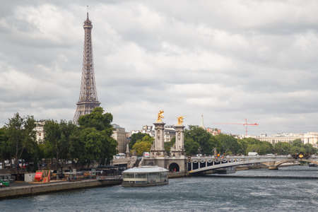 Paris, France - July 13 2019: Boat sailing the Seine river with the Eiffel tower in the background, Paris, France