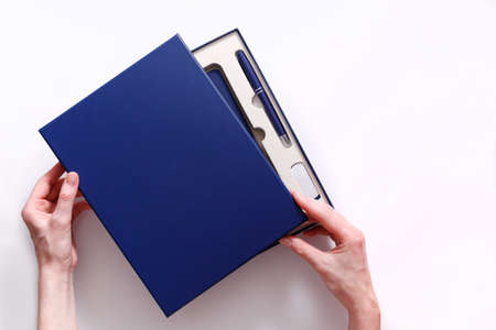Woman hands open cover of corporate style box with pen, flash drive and notebook isolated on white background. View from above