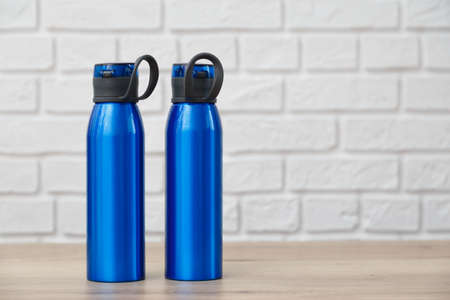 Two blue metal flask . Standing on wooden table with white brick background Zdjęcie Seryjne