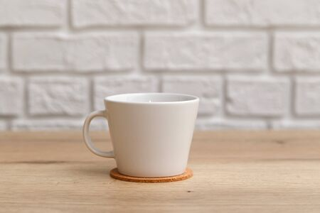 White ceramic cup for coffee on cork coaster on wooden table isolated on white. Reklamní fotografie